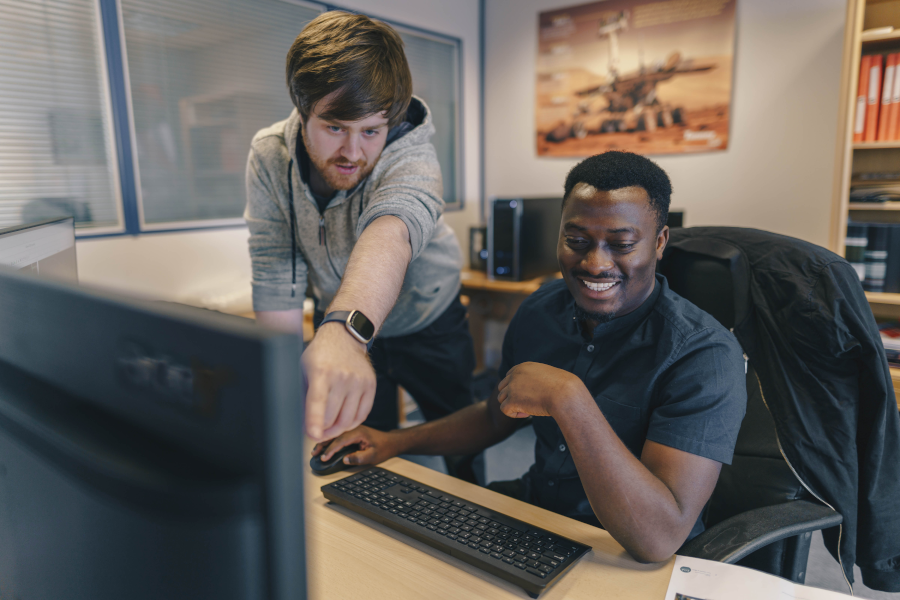 Two EDA Solutions support engineers working on an issue behind a monitor